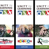 Unity in learning banners for the museum lobby show three vertical banners representing the three branches of this program. The left image shows a child with an aviator helmet on his head giving a thumbs up sign with his left hand. The Yankee air museum logo sits under this picture followed by a solid red bar that reads experience in white text. The center banner shows the close up of a blurry adult in a red shirt with a focused hand towards the cameras foreground holding up something gray and squishy, below it is the Ann Arbor Hands-on Museum logo with a solid blue bar that reads explore in white text. The right banner shows a childs hand, palm down against the wood chip ground. A fuzzy black caterpillar crawls over the hand. Below the image is the Leslie Science and Nature Center logo with a solid green bar that reads discover in white text.