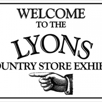 A white sign with old fashion black serif font capital letters says Welcome to the Lions country store exhibit. Named after the donor whos last name is L-Y-O-N-S. At the bottom of the sign a old illustrated hand is pointing to the left
