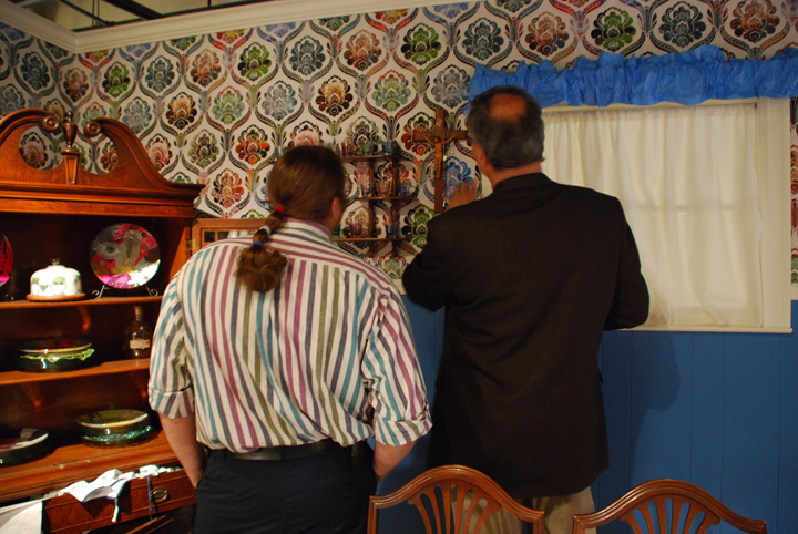 Two men looking at the brigthly colored Victorian style cancer wallpaper and a cross hanging on the wall with rosaries dangling off of it