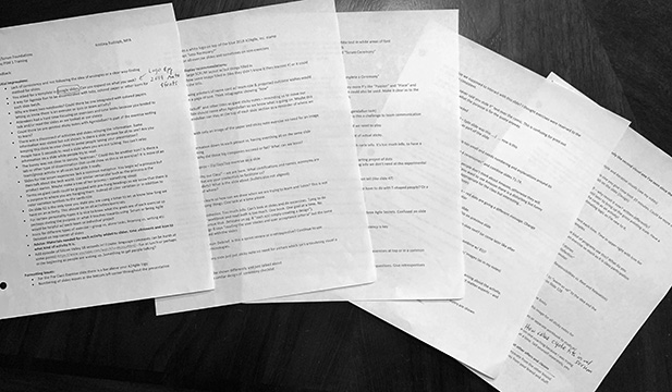5-pages of typewritten letter head sized paper are fanned out against a wood table. The content of the typed notes is not meant to be legible but it covers each page in a 12 point font. A few phrases are hand written in the margins of the top sheet and the bottom right sheet on the right sides.