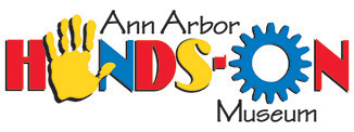 Ann Arbor Hands-On museum logo shows the central word hands-on where the Aye in hand is a yellow hand palm and the letter oh in the word on is a blue gear icon. The H-D, dash mark, and the N are in primary red. The N and gear are in primary blue and the letter S is in yellow to match the hand. Above the word hands-on are written Ann Arbor in black fun, yet readable, font. Centered below the blue oh gear is the word Museum in the same black fun, yet readable font.