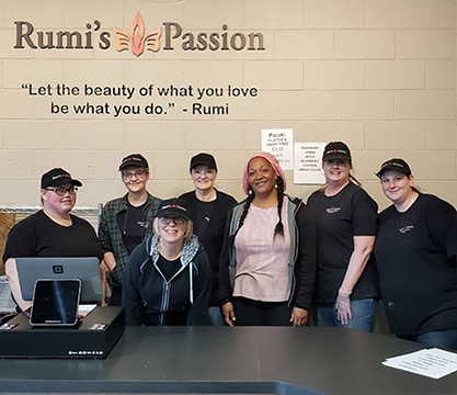 """Seven women  dressed in black t-shirts with the fourth woman over wearing a light pink shirt and goldenrod colored knit cap and side braids. All other women have black hats with white text on them that appear to be the roo me's logo. There dark countertop in front of them as they pose with smiles for the camera. To the left sits a screen with a box on top appearing to be the checkout cash register area. There are some papers in the far right corner laying on the counter which aren't readable. The background wall is painted tan block. Above the women's heads in black lettering it reads """"let the beauty of what you love be what you do."""" dash Roo me spelled R-U-M-I. Above this quote is the Roo me's passion logo."""
