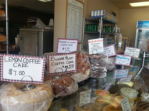 A busy rounded glass front cold case is stocked with cakes and desserts. On top of the case are cakes with signs. From left to right the signs read; lemon coffee cake $7.50, butter rum coffee cake $7.50, rasberry crumb coffee cake $5.95 and some four other offerings which can't be read. Off in the distance is a metal rack with cardboard store boxed items that can't be distinguished.